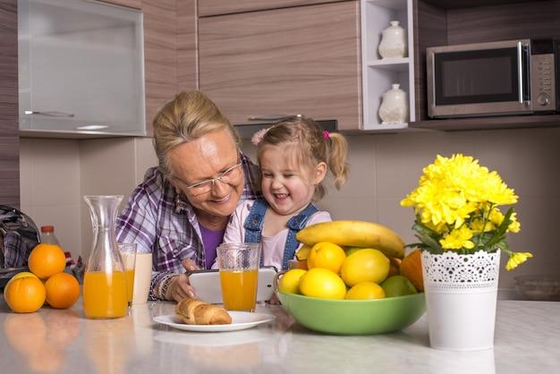 Anciana y su adorable nieta viendo juntos un video divertido en una cocina