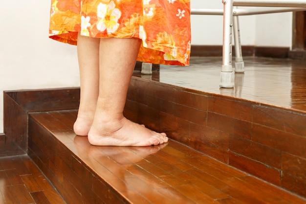 Anciana sube escaleras con andador en casa.