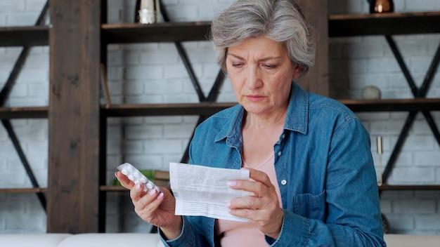Una anciana con tabletas en sus manos y lee un medicamento recetado.