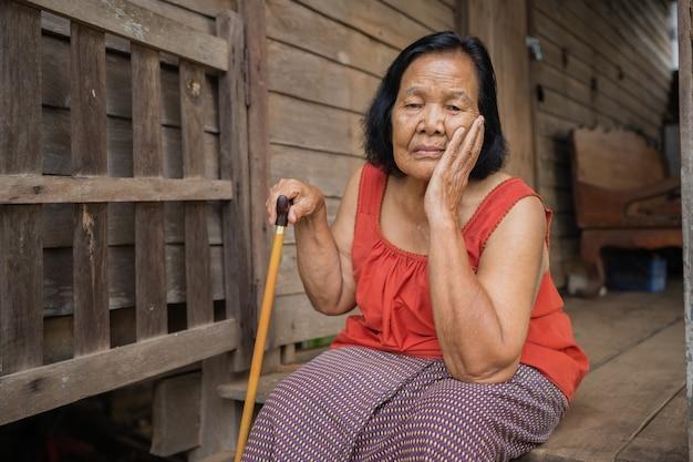 Anciana tailandesa en cuello sin mangas de cuello redondo con dolor de cabeza y rostro estresado preocupado en casa de madera vieja