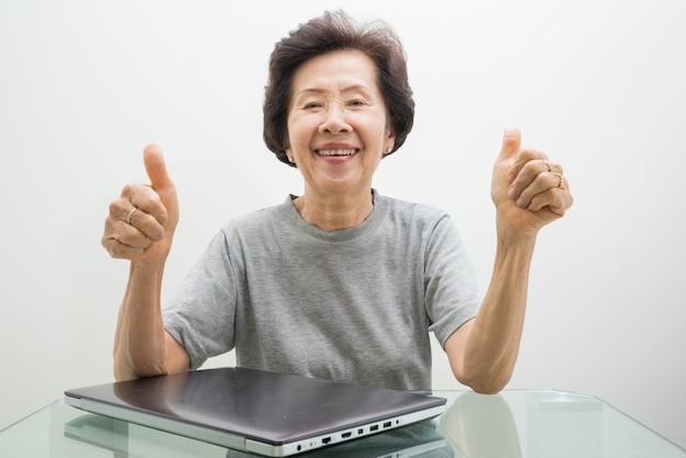 Anciana trabajando con laptop, trabajando con laptop y pulgares arriba