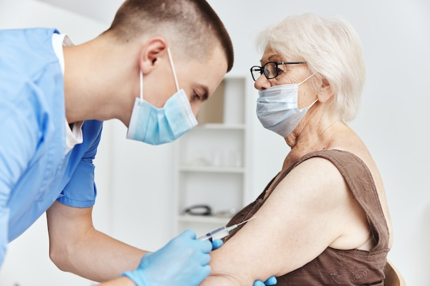 Anciana en el tratamiento del paciente de pasaporte de vacuna de hospital