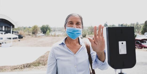 La anciana turista asiática ha comprobado la temperatura corporal con un detector de temperatura térmica para viajes de seguridad.