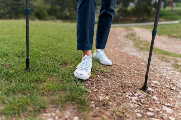 Anciana turista caminando con bastones de senderismo