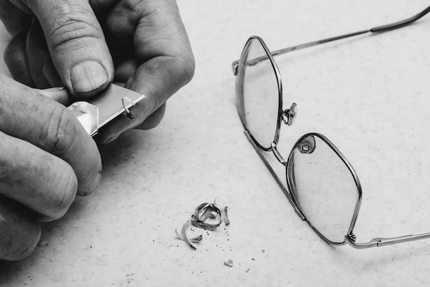 Anciano afila lápiz con cuchillo de oficina. cerca de las manos del viejo hombre.