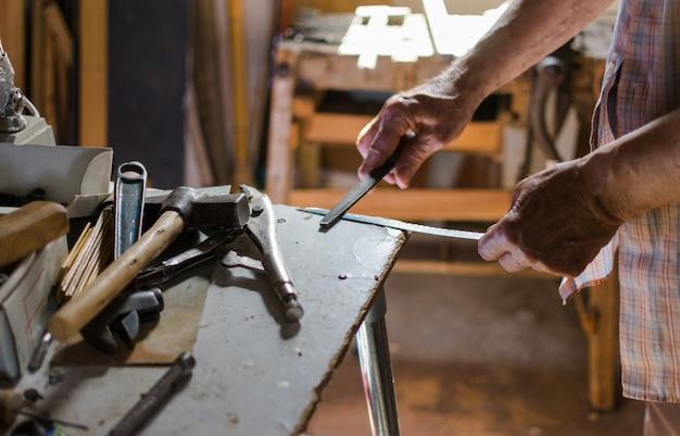 Anciano afilando un cuchillo con una lima