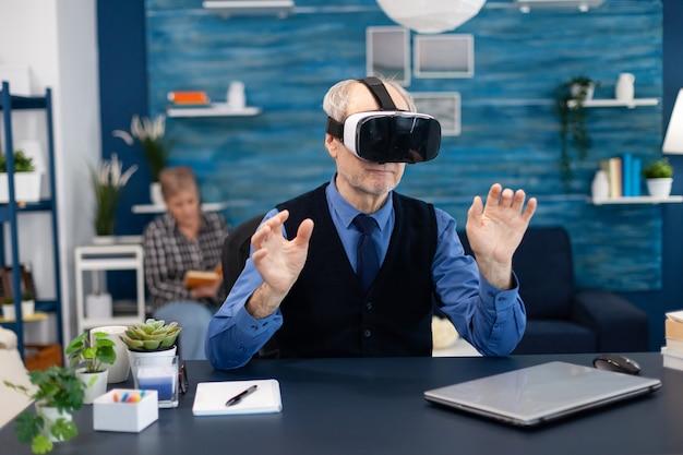 Anciano alegre vistiendo casco de realidad virtual sentado en la oficina de escritorio