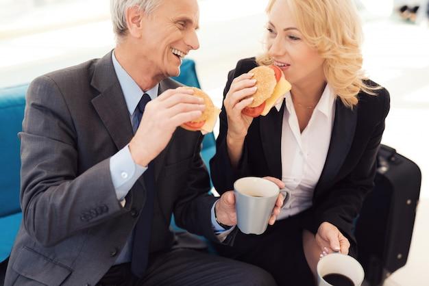 Un anciano y una anciana con traje comen hamburguesas.