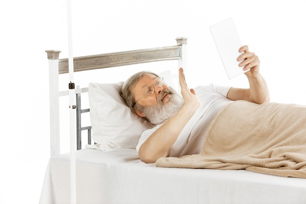 Anciano anciano recuperándose en una cama de hospital aislada