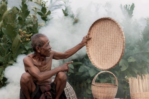 Anciano asiático está mostrando una bandeja de bambú en el campo.