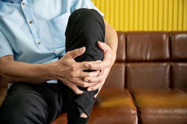 El anciano asiático sentado en safa se lastimó la pierna y la tocó dolorosamente.