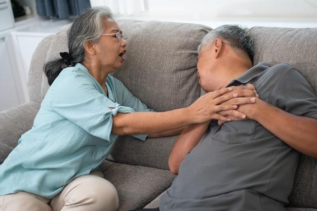 Anciano asiático tiene dolor con las manos en el pecho y tiene un ataque al corazón en la sala de estar