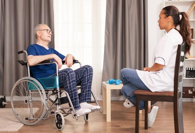 Anciano y asistente discutiendo sobre su accidente y tratamiento.