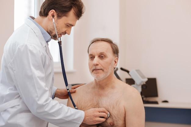 Anciano atractivo hombre tranquilo visitando a su médico para realizar un chequeo regular asegurándose de que esté sano