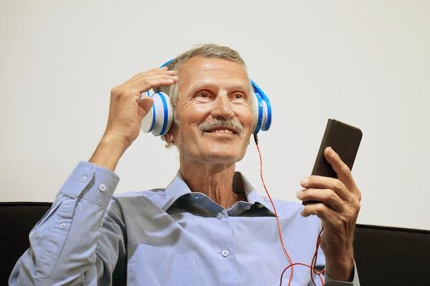 Anciano en auriculares escuchando música