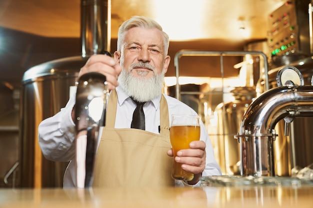 Anciano barman de pie en barra de bar con vaso de cerveza