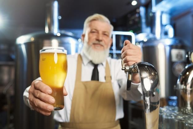 Anciano barman sosteniendo un vaso frío con cerveza lager