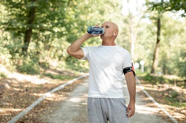 Anciano bebiendo agua en el bosque