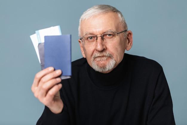 Anciano con billetes de avión y retrato de pasaporte