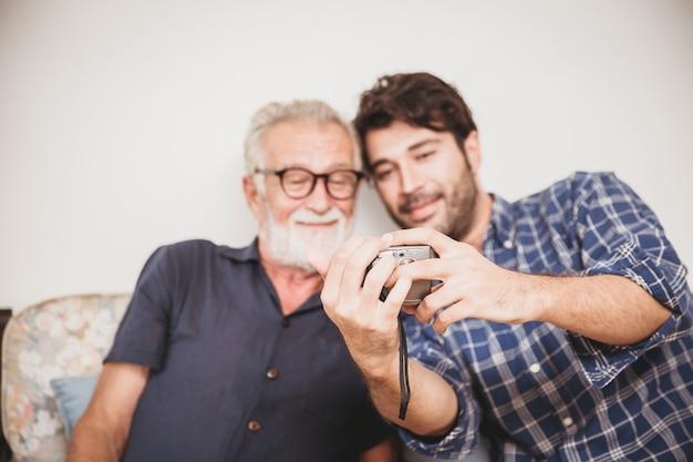 Anciano busca reproducir fotos de la cámara digital con el momento familiar de felicidad de su hijo con el concepto de dispositivo digital.