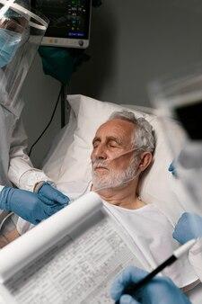 Anciano en una cama de hospital junto a médicos