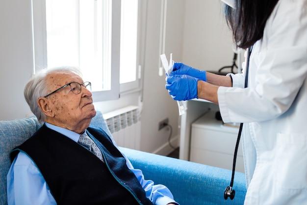 Anciano con camisa azul y corbata mirando a una enfermera mientras abre una prueba de covid. cuidados en el hogar