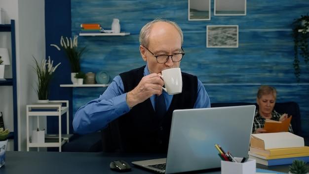 Anciano cansado sentado en el escritorio y tomando un sorbo de café, mirando la computadora portátil trabajando desde el espacio de trabajo en casa mientras su esposa está leyendo un libro en segundo plano. viejo empresario centrado comprobando gráficos