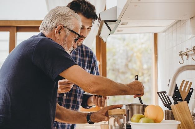 Anciano cocinando en la cocina con su hijo, feliz hombre de familia momento buen mentor anciano cuidado de hijo.