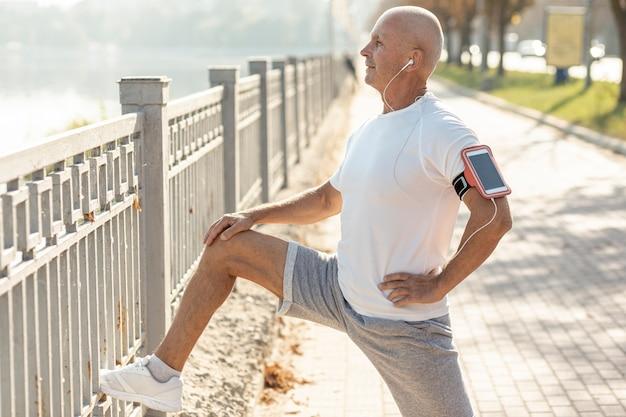 Anciano corredor descansando junto a una valla
