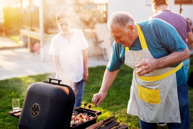 Anciano en un delantal con el vaso en la mano está utilizando su parrilla vintage.