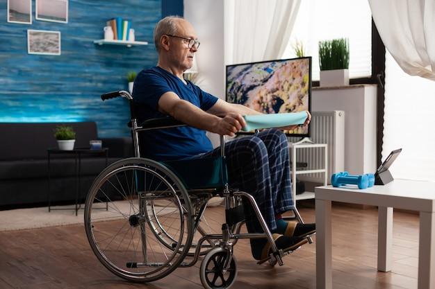 Anciano discapacitado en la resistencia del brazo de entrenamiento en silla de ruedas que ejercita los músculos del cuerpo