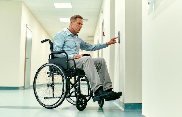 Un anciano discapacitado en silla de ruedas presiona el botón de llamada del ascensor en una clínica moderna.