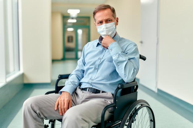 Un anciano discapacitado triste y molesto en silla de ruedas y una máscara médica protectora se sienta en medio del pasillo de una clínica esperando a su familia.