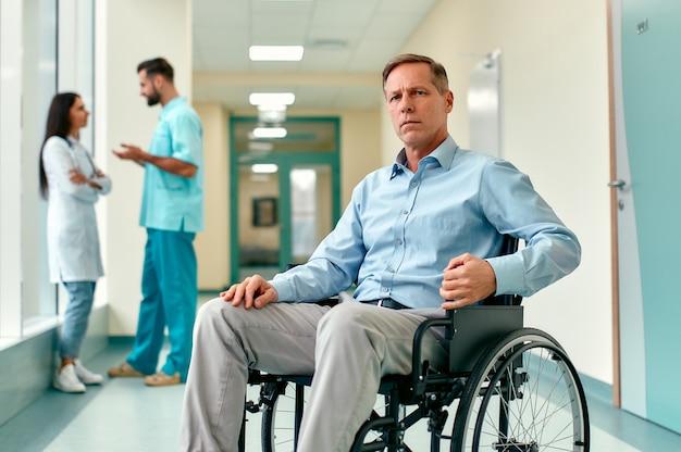 Un anciano discapacitado triste y molesto en silla de ruedas se sienta en medio del pasillo de una clínica esperando a su familia, con los médicos detrás de él.