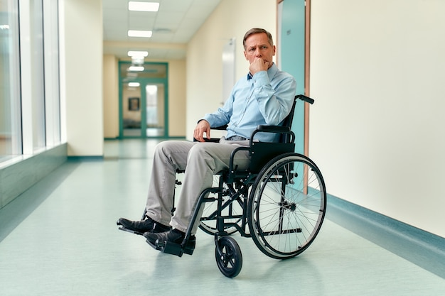 Un anciano discapacitado triste y molesto en silla de ruedas se sienta en medio del pasillo de una clínica esperando a su familia.