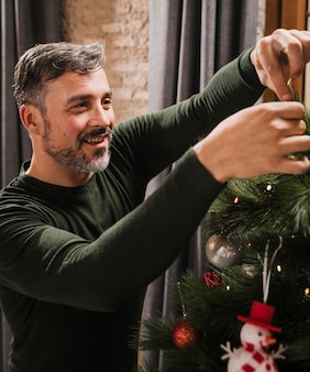 Anciano disfrutando de la decoración del árbol de navidad