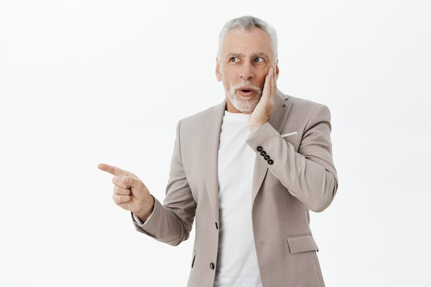 Anciano emocionado y sorprendido en traje apuntando y mirando a la izquierda