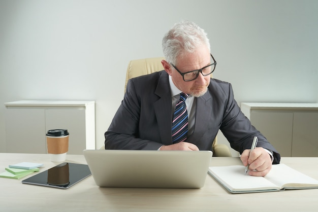 Anciano empresario centrado en el trabajo