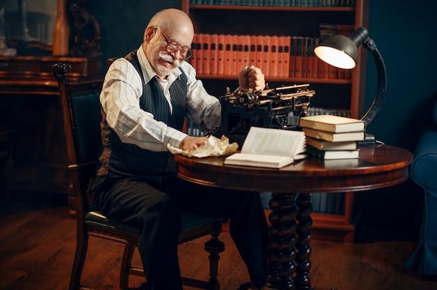 Anciano escritor arruga papel en máquina de escribir vintage en la oficina en casa. anciano con gafas escribe novela literaria en la habitación con humo, inspiración