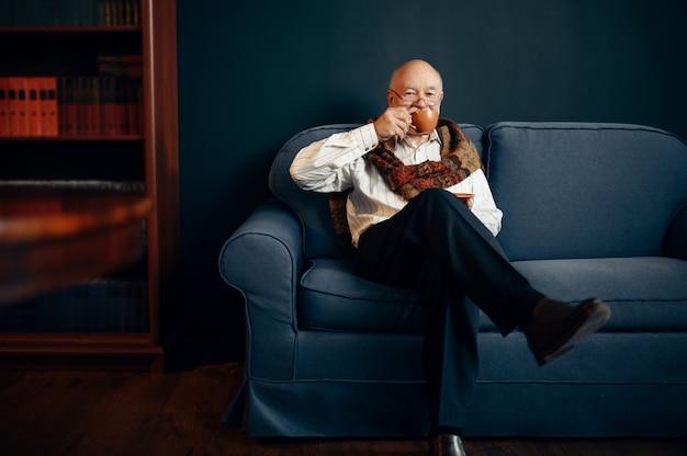 Anciano escritor bebe café en el sofá de la oficina en casa. anciano con gafas escribe novela literaria en la habitación con humo, inspiración