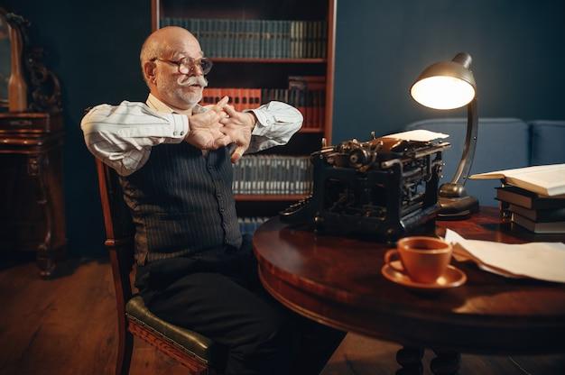 Anciano escritor se prepara para trabajar en máquina de escribir vintage en la oficina en casa. anciano con gafas escribe novela literaria en la habitación con humo, inspiración