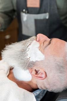 Anciano con espuma de afeitar en cara y cuello.