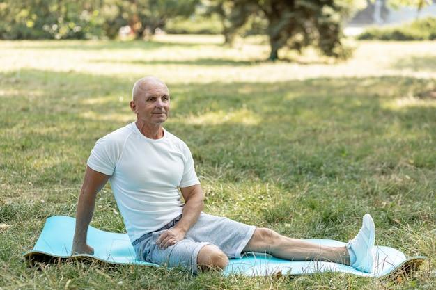 Anciano estirando sobre estera de yoga en la naturaleza