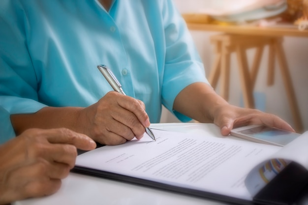 El anciano está firmando un contrato de seguro médico.