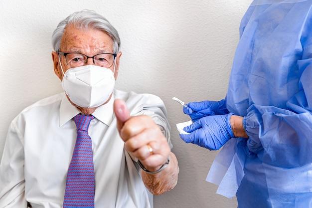 Anciano con gafas y máscara en el interior hace el símbolo de que todo está bien después de la vacunación contra el coronavirus