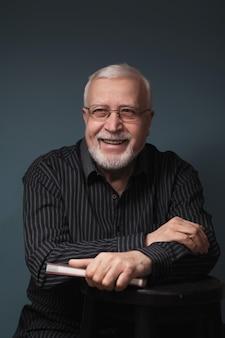 Anciano guapo carismático sentado en vasos con bloc de notas y sonriendo