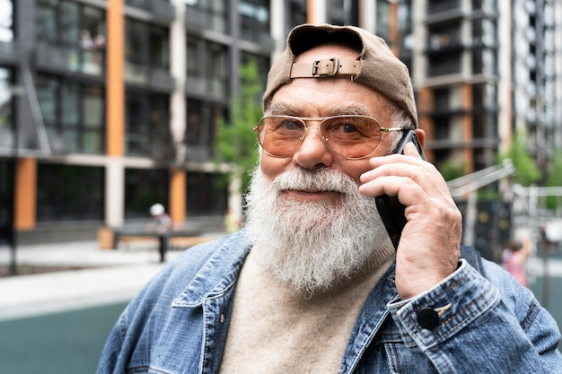 Anciano hablando por teléfono inteligente al aire libre en la ciudad