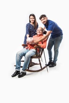 Anciano indio o padre sosteniendo hucha con hijo e hija, sentado sobre una mecedora
