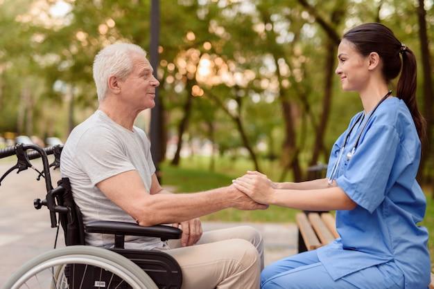 Un anciano con joven enfermera están tomados de la mano