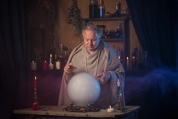 Anciano mago con bola de cristal